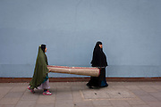 Muslim women carry heavy carpet along street on Walworth Road, Elephant & Castle, London borough of Southwark.