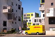 the Kubikon quarter of the GAG Immobilien AG in the Ehrenfeld district of Cologne, DHL parcel service car, Germany.<br /> <br /> das Stadtquartier Kubikon der GAG Immobilien AG im Stadtteil Ehrenfeld, DHL-Fahrzeug, Koeln, Deutschland.