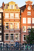 Couple chatting by bicycles and traditional Dutch architecture of canalside buildings in Prinsengracht, Amsterdam, Holland