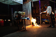 A table dance manager performs a ritual with fire to attract lucky and money for his business during working hours in Ciudad Nezahualcoyotl, March 31, 2011.