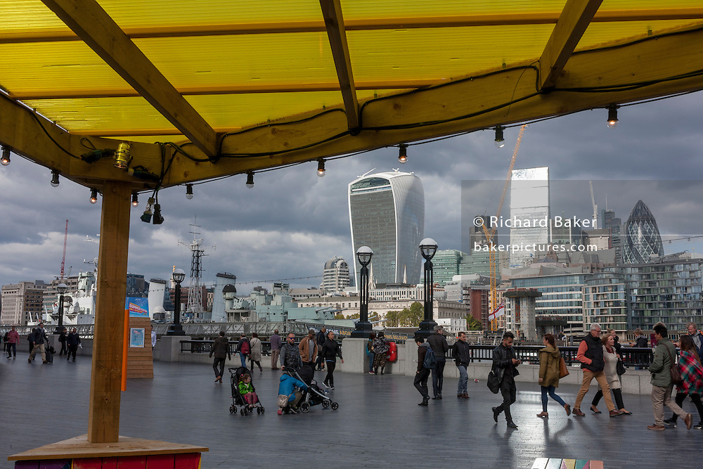 The yellow roof of a themed cafe promoting the capital as a Riviera, with a background panorama looking north from More London in Southwark, towards the City of London.