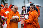 """21 JULY 2013 - BANGKOK, THAILAND:   Buddhist monks at Wat Benchamabophit wait for people to present them with alms on the first day of Vassa, the three-month annual retreat observed by Theravada monks and nuns. On the first day of Vassa (or Buddhist Lent) many Buddhists visit their temples to """"make merit."""" During Vassa, monks and nuns remain inside monasteries and temple grounds, devoting their time to intensive meditation and study. Laypeople support the monastic sangha by bringing food, candles and other offerings to temples. Laypeople also often observe Vassa by giving up something, such as smoking or eating meat. For this reason, westerners sometimes call Vassa the """"Buddhist Lent.""""      PHOTO BY JACK KURTZ"""