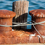 Large rusting cleat for tying up fishing vessels on an old pier in Gloucester, Massachusetts