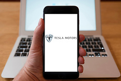 Using iPhone smartphone to display logo of Tesla, manufacturer of electric cars