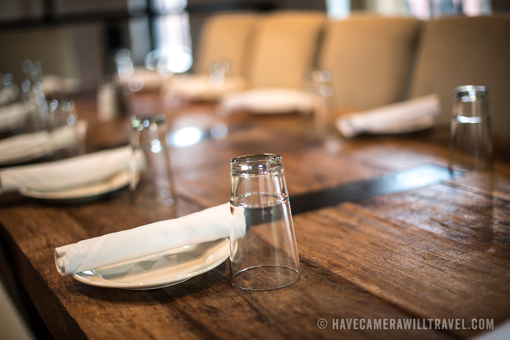 A simple table setting in a restaurant on a solid wooden table.