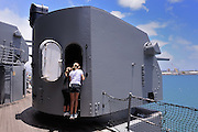 2 children (8 years old, 11 years old) peer into gun turret on the USS Missouri. Battleship Missouri Memorial, Pearl Harbour, Hawaii RIGHTS MANAGED LICENSE AVAILABLE FROM www.PhotoLibrary.com