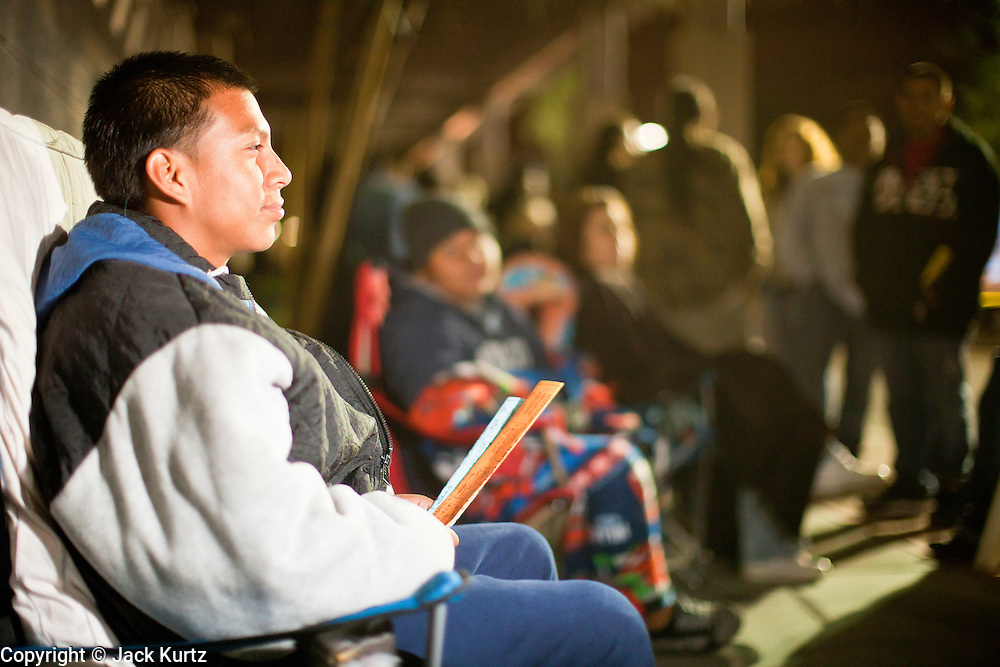 """24 NOVEMBER 2011 - PHOENIX, AZ:  Joe Martinez (CQ), 15, was first in line at the Best Buy store on Thunderbird and I 17 in Phoenix Thursday night. He said he got in line after school on Tuesday and was in line to buy the 42"""" Sharp TV. """"Black Friday,"""" the unofficial start of the holiday shopping season started even earlier than normal. Many stores, including Target and Best Buy, opened at midnight. The Best Buy at Thunderbird and I 17 showed a Harry Potter movie on the side of a rented truck in the parking lot to keep people amused while they waited for the store to open.   Photo by Jack Kurtz"""