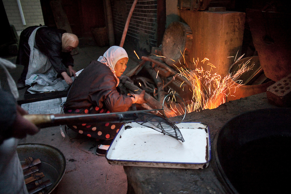 Women stoke cooking fires at the Wangjia Hutonng Womens' Mosque in the early morning. The women are making a special fried bread to be given out to commemorate the death of a friend.