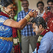 A bride in Thiruvananthapuram breaks a Papad (poppadum) over the groom's head as part of the post wedding games aimed at breaking the ice between the newlyweds who traditionally would not have met before the wedding. Kerala, 2012