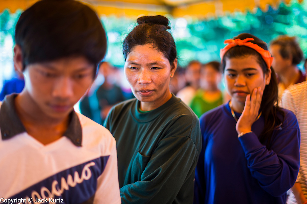 """17 JULY 2014 - BANGKOK, THAILAND:  Undocumented Cambodian construction workers wait for temporary ID cards at the temporary """"one stop service center"""" in the Bangkok Youth Center in central Bangkok. Thai immigration officials have opened several temporary """"one stop service centers"""" in Bangkok to register undocumented immigrants and issue them temporary ID cards and work permits. The temporary centers will be open until August 14.   PHOTO BY JACK KURTZ"""