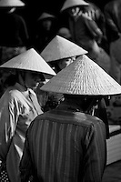 Women in conical hats gathered together at the fish market in Hoi An.