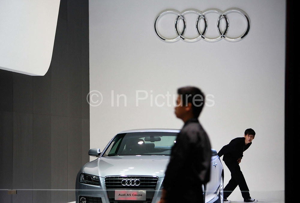 A exhibition staff looks at an Audi AG vehicle during the China ( Guangzhou) International Automobile Exhibition in Guangzhou, Guangdong Province, China, on Monday, Nov. 21, 2011. Despite signs of slowing, China remains the largest and fastest growing market for international car makers, especially in the luxury sector.