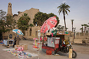 A tourist stall with Coca-Cola umbrella in Luxor Square, with the Mosque of Abu el-Haggag's minaret, far left, Luxor Temple, Nile Valley, Egypt. A stall holder is in the background and waits for visitors to this central location - a passing point for tourism. According to the country's Ministry of Tourism, European visitors to Egypt is down by up to 80% in 2016 from the suspension of flights after the downing of the Russian airliner in Oct 2015. Euro-tourism accounts for 27% of the total flow and in total, tourism accounts for 11.3% of Egypt's GDP.