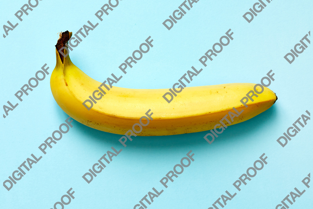 Close up of a ripe banana isolated on blue background.