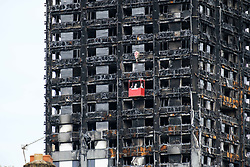 August 16, 2017 - London, UK - Workmen in a crane outside the Grenfell residential tower block in West London are seen wrapping the tower with a cling film type material. The tower was engulfed by a fire two months ago causing at least 80 deaths and over 70 injuries. Up to 200 survivors are still living in hotels and have resorted to searching for new homes themselves out of frustration at the council's rehousing efforts. (Credit Image: © Ray Tang via ZUMA Wire)