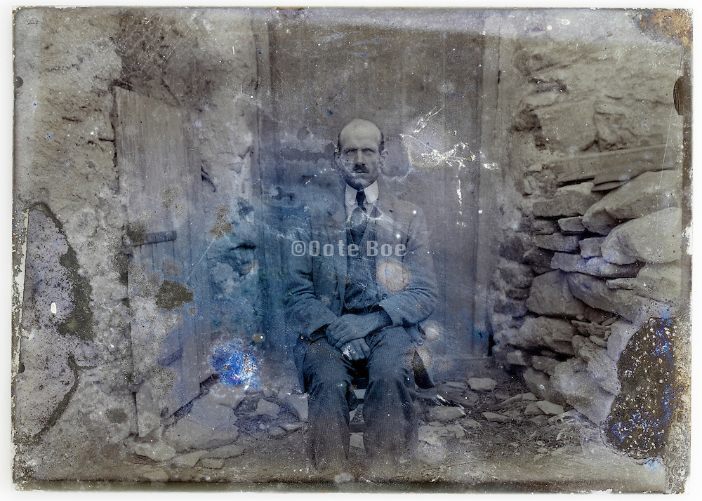 eroded glass plate with an adult man sitting in front of door