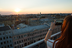 A woman photographs the sun setting over the city of St Petersburg, Russia, on the eve of England's 3rd/4th place World Cup match against Belgium.