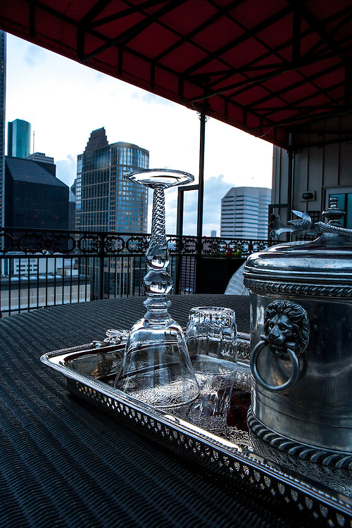 Houston, Texas skyscrapers viewed from residential balcony of luxury high-rise at sunset with romantic tray of elegant wine glasses and ice bucket.