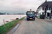 Nederland, Ooij, 01-02-1995Eind januari, begin februari 1995 steeg het water van de Rijn, Maas en Waal tot record hoogte van 16,64 m. bij Lobith. Een evacuatie van 250.000 mensen was noodzakelijk vanwege het gevaar voor dijkdoorbraak en overstroming. op verschillende zwakke punten werd geprobeerd de dijken te versterken met zandzakken. Hier in de Ooijpolder bij Nijmegen patrouilleert de politie langs de lege huizen.Late January, early February 1995 increased the water of the Rhine, Maas and Waal to a record high of 16.64 meters at Lobith. An evacuation of 250,000 people was needed because of flood risk. At several points people tried to reinforce the dikes with sandbags. Here in the Ooijpolder in Nijmegen.Foto: Flip Franssen/Hollandse Hoogte