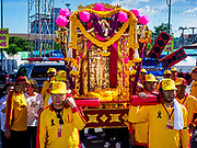 """02 JUNE 2017 - SAMUT SAKHON, THAILAND: Men carry the City Pillar Shrine to waiting boats in Samut Sakhon. The Chaopho Lak Mueang Procession (City Pillar Shrine Procession) is a religious festival that takes place in June in front of city hall in Samut Sakhon. The """"Chaopho Lak Mueang"""" is  placed on a fishing boat and taken across the Tha Chin River from Talat Maha Chai to Tha Chalom in the area of Wat Suwannaram and then paraded through the community before returning to the temple in Samut Sakhon. Samut Sakhon is always known by its historic name of Mahachai.      PHOTO BY JACK KURTZ"""