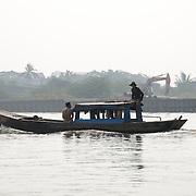 A sampan travels down the Saigon River in Ho Chi Minh City, Vietnam.
