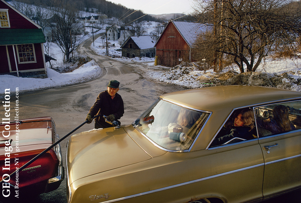 Gas station attendant pumps gasoline fuel into a 1960's automobile on a winter morning at a general store in East Topsham, Vermont. The store is Freddie Miller's General Store in rural Vermont with muddy roads and snow. Freddie uses a hose and nozzle attached to a gas pump.