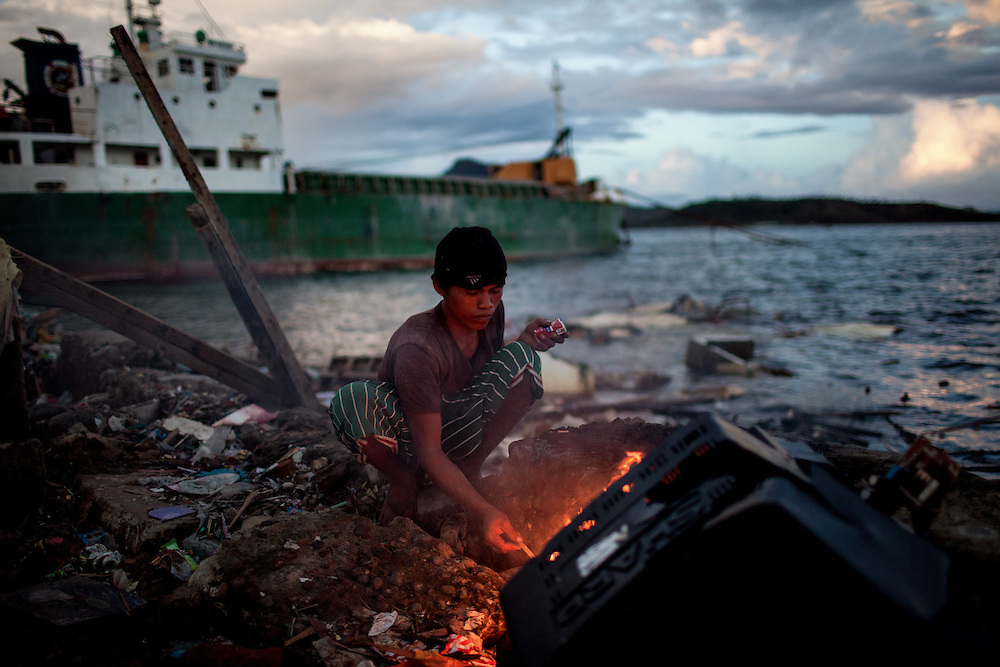 A man makes a fire using scraps of broken woods and plastic scattered on the shore.
