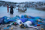 EDITORS NOTE: Image contains nudity. Ocean Rebellion staged their final action in their sequence of theatrical protests on the 11th June 2021 on Harbour beach, St Ives, Cornwall, United Kingdom. A mass stranding of mermaids, tangled in discarded trawler nets, washed up on a beach near the gathering of the G7 heads of state. The G7 summit will take place. The G7 summit held in Carbis Bay between June 11-13 and will see world leaders gather to discuss some of the most pressing challenges facing us, from climate change to tackling the ongoing Covid-19 pandemic.