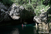 cave tubing guide rides the Caves Branch River into a cave on the grounds of Jaguar Paw Jungle Resort, Cayo District, Belize, Central America