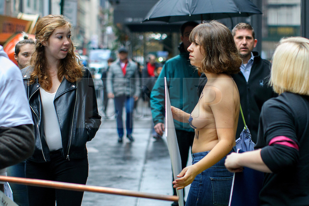 © Licensed to London News Pictures. 09/11/2016. New York CIty, USA. A topless anti-Trump campaigner is heckled whilst protesting outside Trump Tower in New York City, on Wednesday, 9 November 2016 following the presidential election won by Donald Trump. Photo credit: Tolga Akmen/LNP