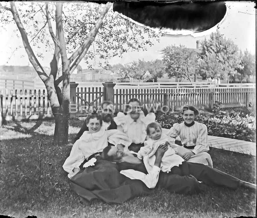 The man Identified as Oliver Cooley is laying down holding the baby. Batavia Historical Society knows that Oliver Cooley lived on the corner of College and Spring Streets.