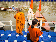 12 FEBRUARY 2015 - BANGKOK, THAILAND: A Buddhist monk looks out over the water at the floating market opened on Khlong Phadung Krung Kasem, a 5.5 kilometre long canal dug as a moat around Bangkok in the 1850s. The floating market opened at the north end of the canal near Government House, which is the office of the Prime Minister. The floating market was the idea of Thai Prime Minister General Prayuth Chan-ocha. The market will be open until March 1.    PHOTO BY JACK KURTZ
