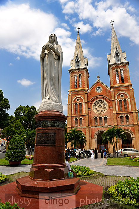 A wedding party assembles between the Gothic Revival styled Saigon Notre-Dame Cathedral Basilica, and a granite statue of the Virgin Mary. The cathedral was built between 1863 and 1880, the statue was installed in 1959. Ho Chi Minh City (Saigon), Vietnam