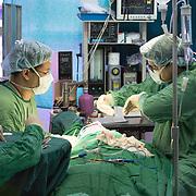 CAPTION: While performing Allison's operation, Dr Luis González takes a break to explain to his assistant surgeon how to prevent fistulas. LOCATION: Hospital Escuela, Tegucigalpa, Honduras. INDIVIDUAL(S) PHOTOGRAPHED: Dr Emerson Gabriel Medina (left) and Dr Luis González (right).