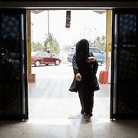 Woman wearing a face veil enters the airport in Salalah, a more culturally conservative region of Oman near the Yemeni border. Salalah, the capital of the Dhofar Governorate, was once the the largest frankincence producing region in the world.