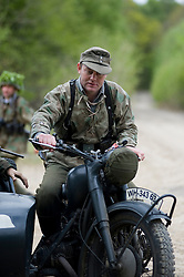Reenactors from Northern World War Two Association, portraying members of the Grossdeutschland division riding a motorcycle and sidecar combination during a 24hr private exercise, held at Sutton Grange, near Ripon in Yorkshire. The white steel helmet or Stahlhelm marked on the front of the sidecar is the Großdeutschland Division tactical symbol, <br />