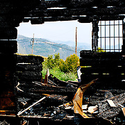 Wood log house burnt by fire to black coal