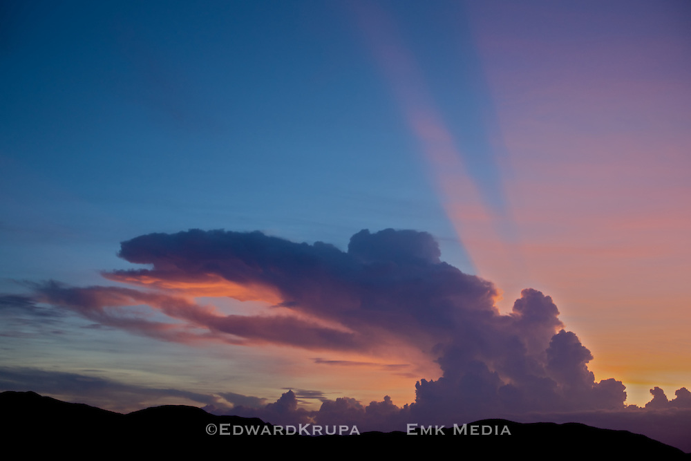 Dramatic cloud formation enhances a radiant sunset over a mountain ridge in China.