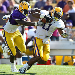 April 9, 2011; Baton Rouge, LA, USA; LSU Tigers running back Spencer Ware (11) breaks away from linebacker Lamin Barrow (57) during the 2011 Spring Game at Tiger Stadium.   Mandatory Credit: Derick E. Hingle