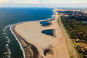 Nederland, Zuid-Holland, Gemeente Westland, 15-07-2012; Delflandse Kust ter hoogte van Ter Heijde en Monster, Den Haag aan de horizon..De Zandmotor is een kunstmatig schiereiland ontstaan door het opspuiten van zand voor de kust. Wind, golven en stroming zullen het zand langs de kust verspreiden waardoor breder stranden en duinen ontstaan. De zandmotor is een experiment in het kader van kustonderhoud en kustverdediging. .Sand Engine, artificial peninsula build by the raising of sand for the coast of Ter Heijde (near the Hague, at the horizon). Wind, waves and currents will distribute the sand along the coast yielding wider beaches and dunes along the coastline. The Sand Engine is a experiment for coastal maintenance of coastal defense..luchtfoto (toeslag); aerial photo (additional fee required) foto Siebe Swart / photo Siebe Swart