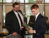 """Bernie Campbell (Drama) and John Hammond reminisce about  their first play of the school year """"The Origin of Species and The Descent of Man"""" Darwin after Campbell gives Hammond the book as a gift during the Top Ten dinner at the Huot Center on Thursday evening.   (Karen Bobotas/for the Laconia Daily Sun)"""