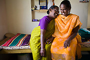 An elderly resident shares a joke with her social worker in her room at the Tamaraikulam Elders' Village