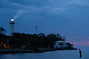 The light from the St. Simons Lighthouse penetrates the dawn at Couper's Point along the Saint Simons Sound in St. Simons Island, Georgia. The working lighthouse was built in first constructed in 1807 but destroyed by Confederate forces in 1862 before being rebuilt in 1872.