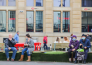 25th February, Cheltenham, England. Shoppers sat on outside benches during the third national lockdown.