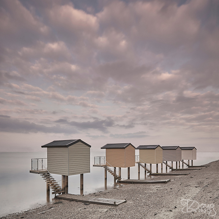 A line of pastel coloured beach huts standing on stilts at the edge of the water at Heybridge Basin in Essex under pink dawn clouds.