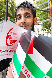London, August 23rd, 2014. A young man raises funds for Islamic Help by selling Palestinian flags as  hundreds of pro- Palestine protesters demonstrate outside Downing Street demanding that Britain stops arming Israel.