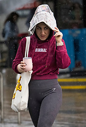 © Licensed to London News Pictures. 07/08/2021. London, UK. A member of the public shelters underneath a newspaper as she gets caught in a downpour of rain in Wood Green, North London. Heavy rain is expected to cause flash flooding in parts of the UK. Photo credit: Ben Cawthra/LNP