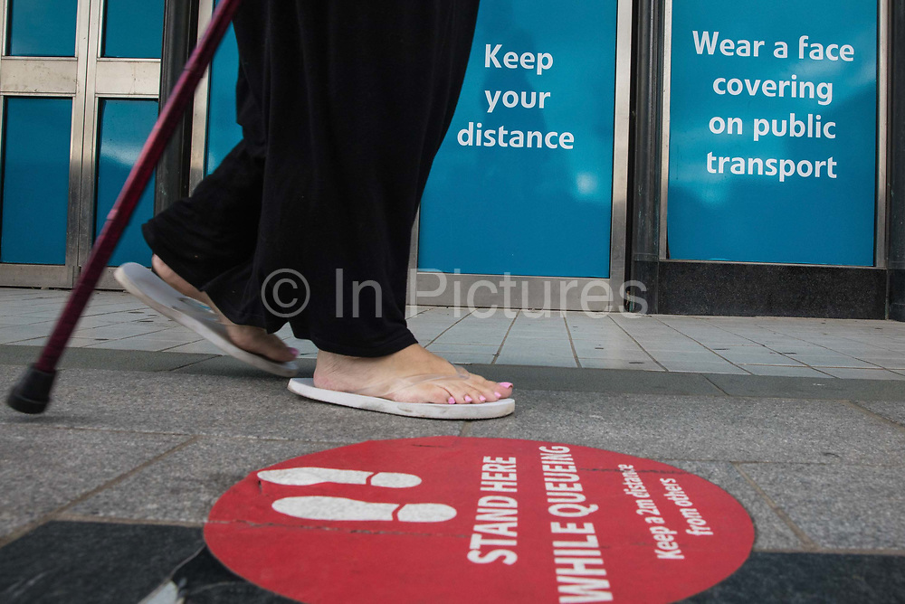 A member of the public walks past COVID-19 post lockdown public information displays on 21st August 2020 in Slough, United Kingdom. Slough has been listed by Public Health England PHE and the Department for Health and Social Care DHSC as an 'area of concern' for COVID-19 following a rise in positive coronavirus cases over the last two weeks.
