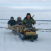 North of the Arctic Circle in Russia, a mechanic from Nizhnyaya Pesha carries Andrei Volkov and Andrew MacLean in a sled behind his crude Russian snowmobile. They are en route to visit the ever-moving camp of the last nomadic Komi reindeer-herding clan.  The rifle is for protection against bears.