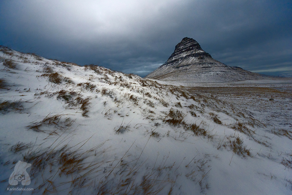 Carved during the last Ice Age, the world-renowned Kirkjufell mountain (Church Mountain) located in the Snæfellsnes peninsula, near the small town of Grundarfjörður in Western Iceland. The 463m tall Kirkjufell is one of the most photographed landmarks in Iceland and hiking to the top is a treacherous adventure. A few hundred meters from the reverse side of the mountain is Kvíabryggja, a prison without bars of fences, where inmates carry out farming duties.